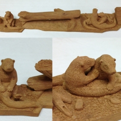 Member carving - otters in cottonwood bark