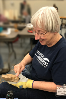 Diane Turck smiles while carving a fish