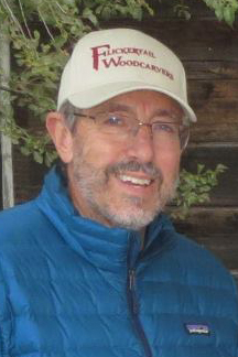 Doug Emerson smiles at the camera while wearing a Flickertail Woodcarvers hat